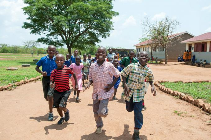 Children run to school in central Uganda