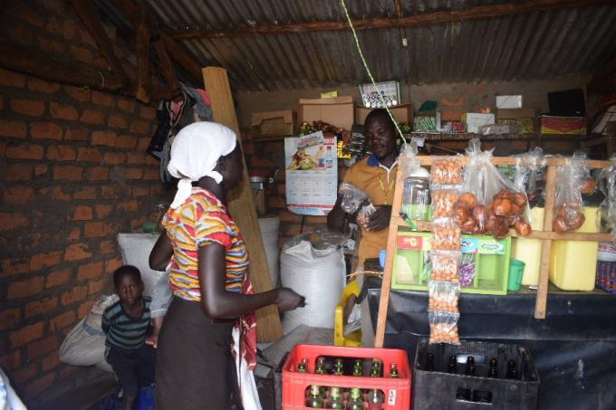 Opio, 21, serves a customer in his new shop