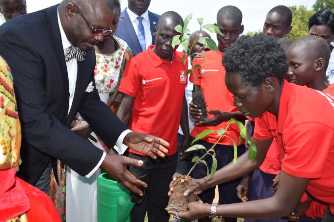 Hon. Oulanya receives a tree seedling to plant