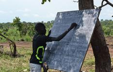 Refugee children from South Sudan have their class under a tree in Ayilo I resettlement camp, Adjumani district, Uganda