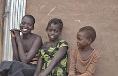 Fostered children Jacqueline Wani* (14), Grace Wani* (11) and Mario Wani* (8) outside their hut in Baratuku refugee resettlement camp, Adjumani district, Uganda