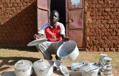 Patrick Otukene poses with some of his products outside his shop.